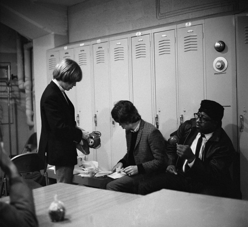 Brian and Mick checking out gifts and fanmail, Chicago (28 November 1965)  In the principal cities, it was usual practice for several local bands and celebrities to join the bill, and in Chicago, the legendary Blues man Bo Diddley turned up bearing gifts of toffee apples