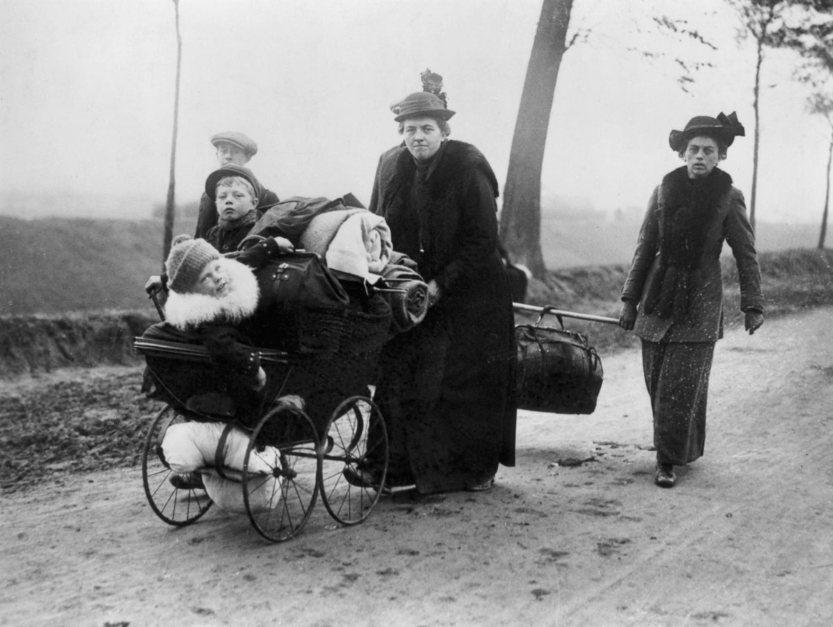 1914 Belgian refugees carry their belongings ahead of invading troops through Northern France.