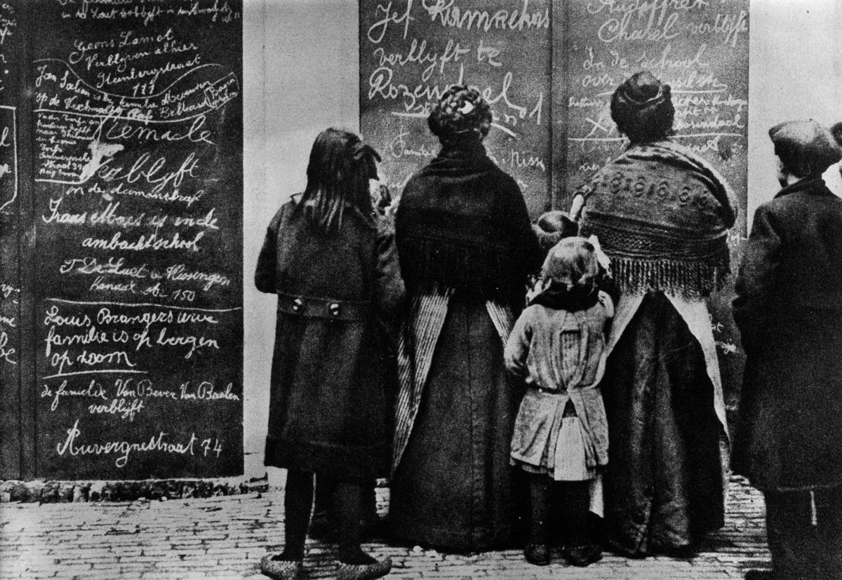 1915 Belgian refugees read Flemish messages left by other refugees in a French town.