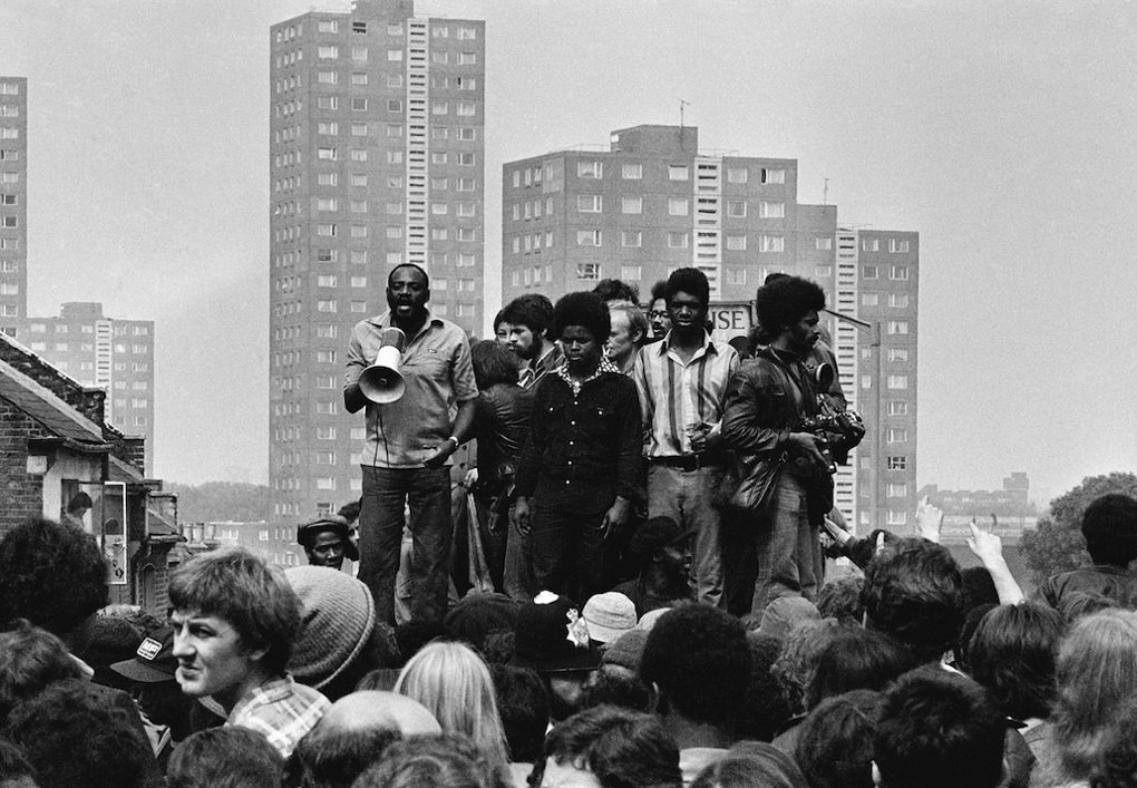 Darcus Howe (with loudhailer) addresses a crowd from on top of a toilet block, 1977.