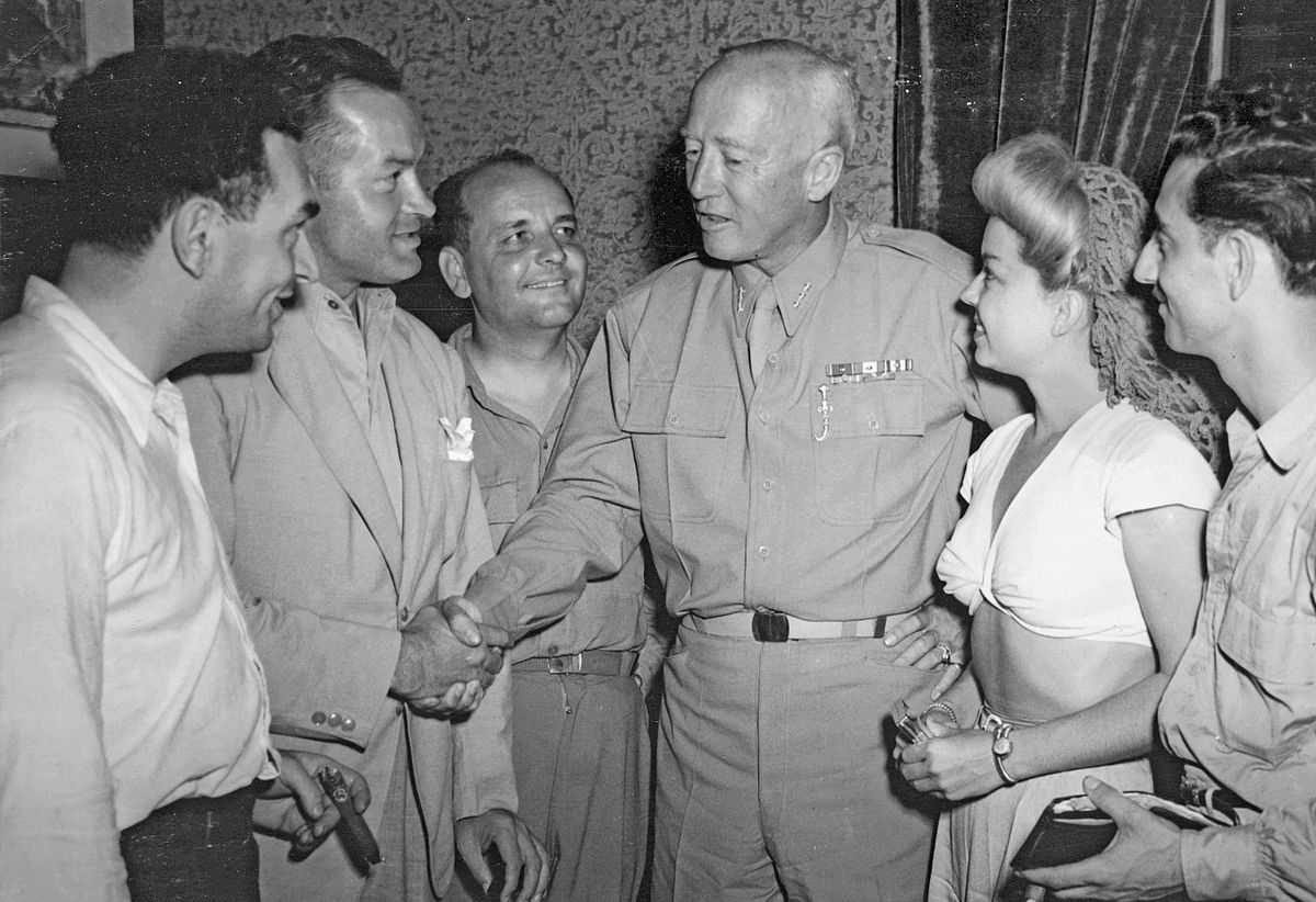 """left to right: Hal Block, Bob Hope, Barney Dean, General George S. Patton, Frances Langford and Tony Romano. Sicily, August 21, 1943. Significance of photo: Bob Hope and his USO troupe arrived in Sicily three days after the Seventh Army took the key town of Messina. Patton asked Hope to tell his radio audience """"that I love my men."""" This was soon after Patton had slapped two hospitalized soldiers accusing them of cowardice. Patton was attempting to appear more compassionate during Hope's visit."""