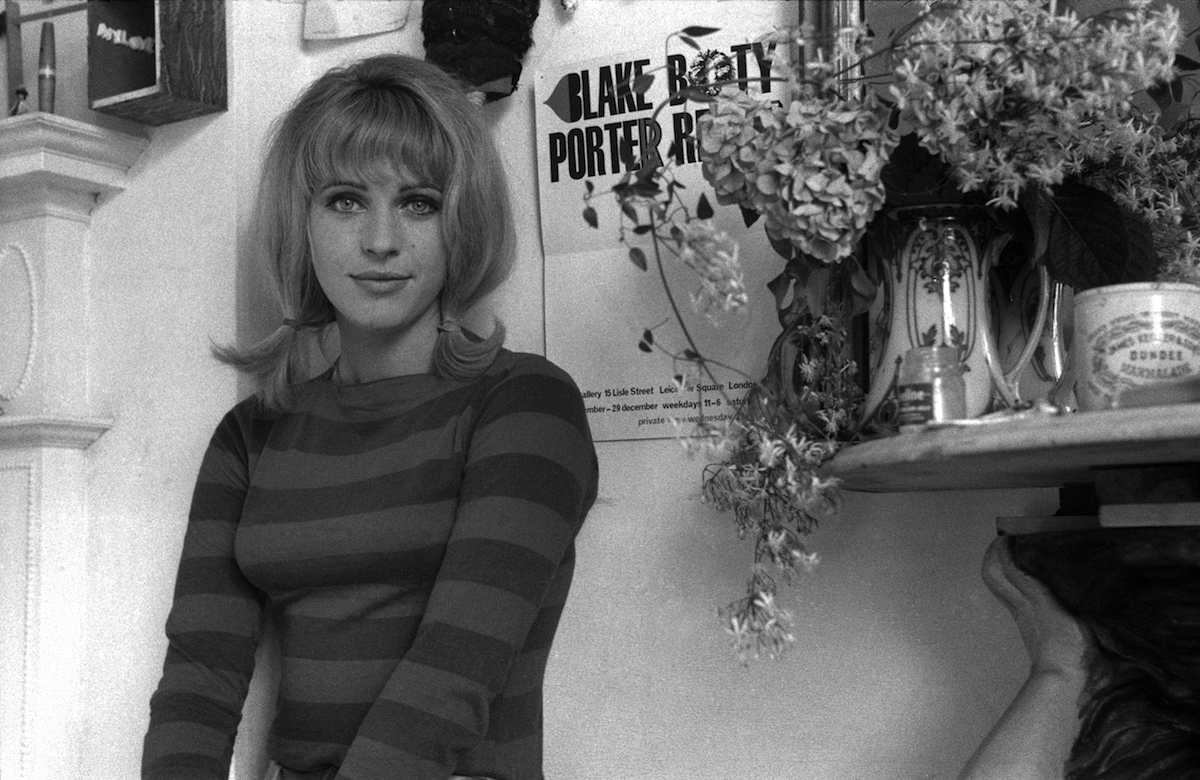 Pauline Boty by John Aston, 1962. The poster for the pop-art exhibition is behind her.