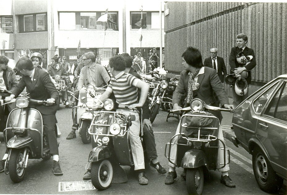 Mods on scooters in the Carnaby Street area of London being filmed for 'Steppin' Out', summer 1979. On the far right of the photo (holding crash helmets) is Mick Talbot of mod band The Merton Parkas.