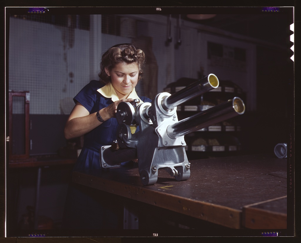 A young woman employee of North American Aviation, Incorporated, working over the landing gear mechanism of a P-51 fighter plane, Inglewood, Calif. The mechanism resembles a small cannon