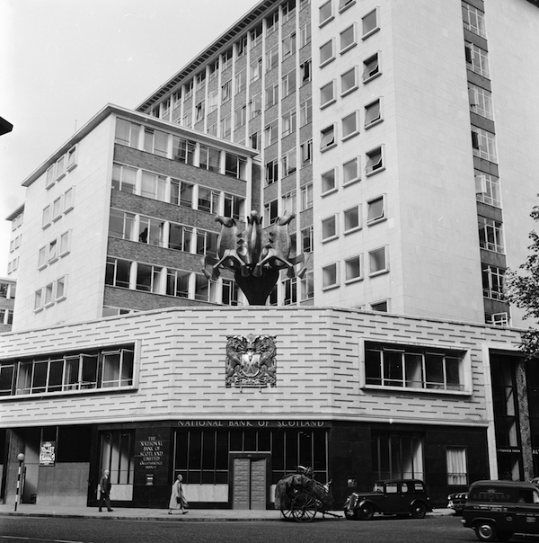 August 1958: The Knightsbridge branch of the National Bank of Scotland, with a modern sculpture of three rearing horses atop the entrance. (Photo by Howell Evans/BIPs/Getty Images)