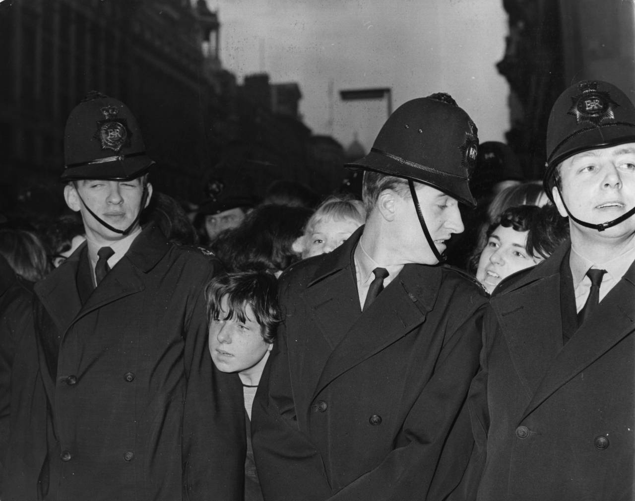 20th March 1964: A young Beatles fan pushes her head between the shoulders of two policemen on duty outside Television House, Kingsway, London, where the Beatles are expected to appear on the ITV pop programme 'Ready, Steady, Go!' (Photo by Kent Gavin/Keystone/Getty Images)