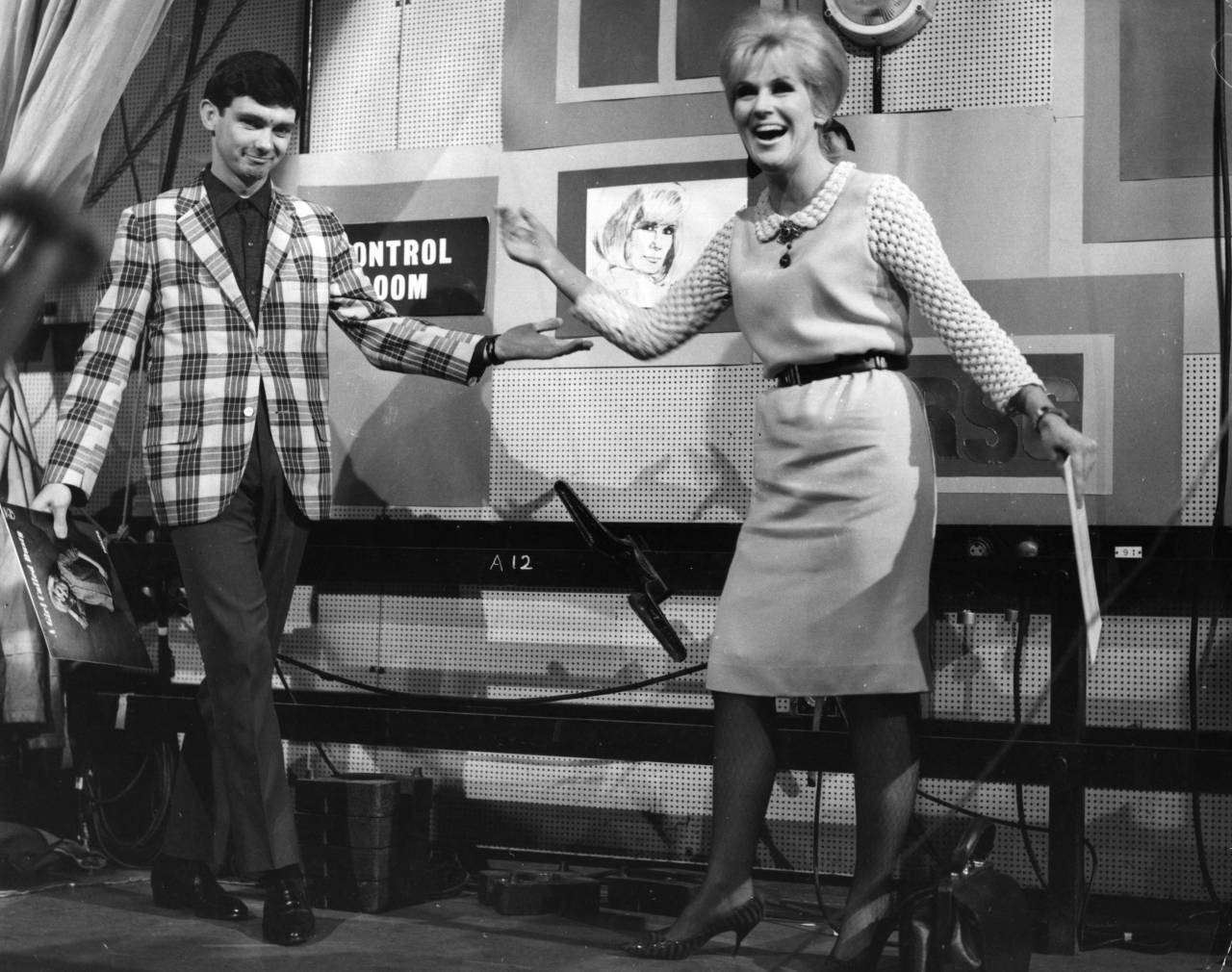 November 1964: Pop singers Gene Pitney and Dusty Springfield (1939 - 1999), holding copies of each others records, share a joke on the set of British television music show 'Ready Steady Go'. (Photo by Chris Ware/Keystone Features/Getty Images)