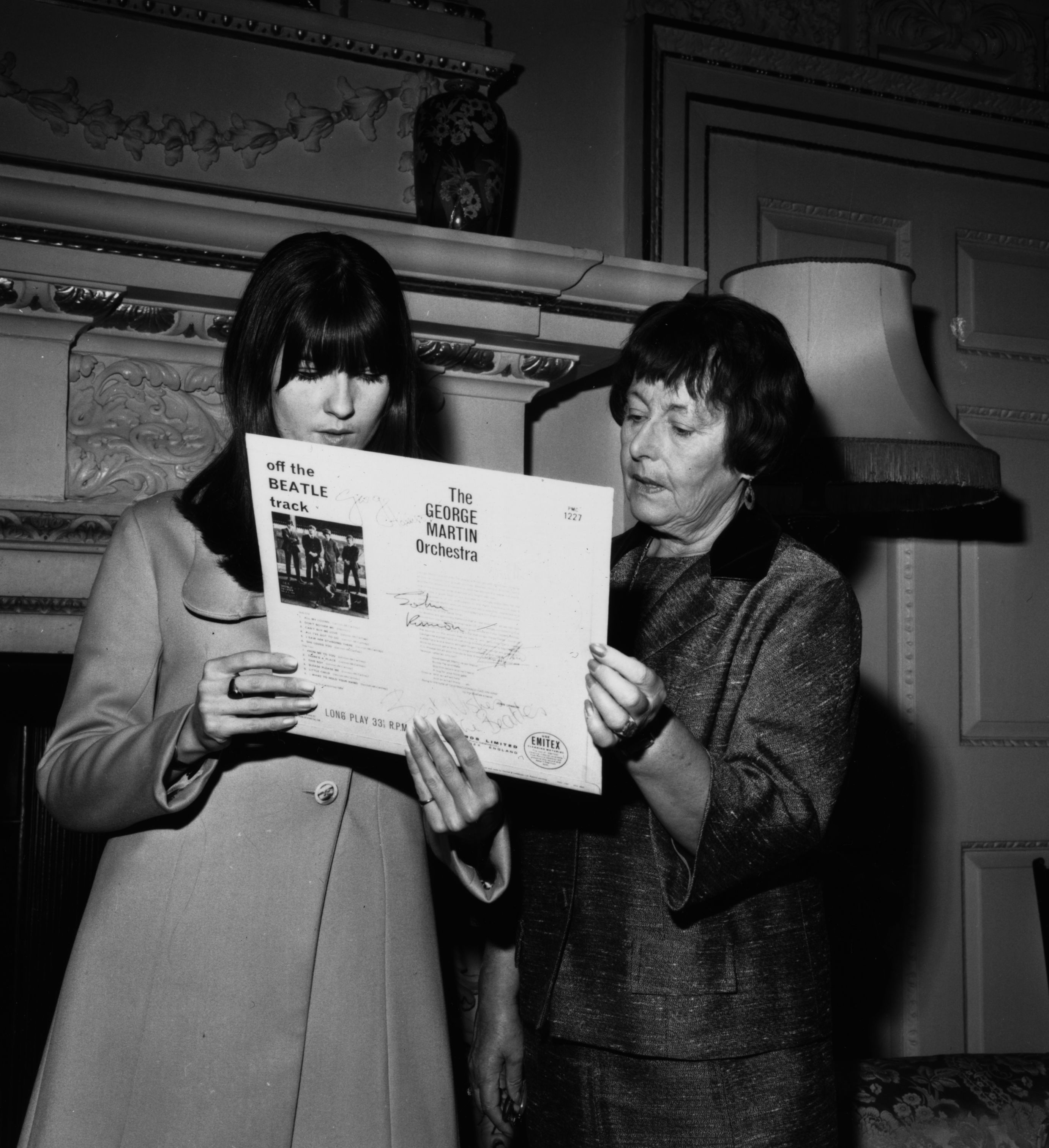 25th November 1965: Hostess of the television pop programme 'Ready Steady Go' Cathy McGowan presents a signed Beatles record to Lady Mayoress Denny at the Mansion House, London. The record is donated by the Beatles as a raffle prize for the British Red Cross Society's City of London Branch Fair. (Photo by Keystone/Getty Images)