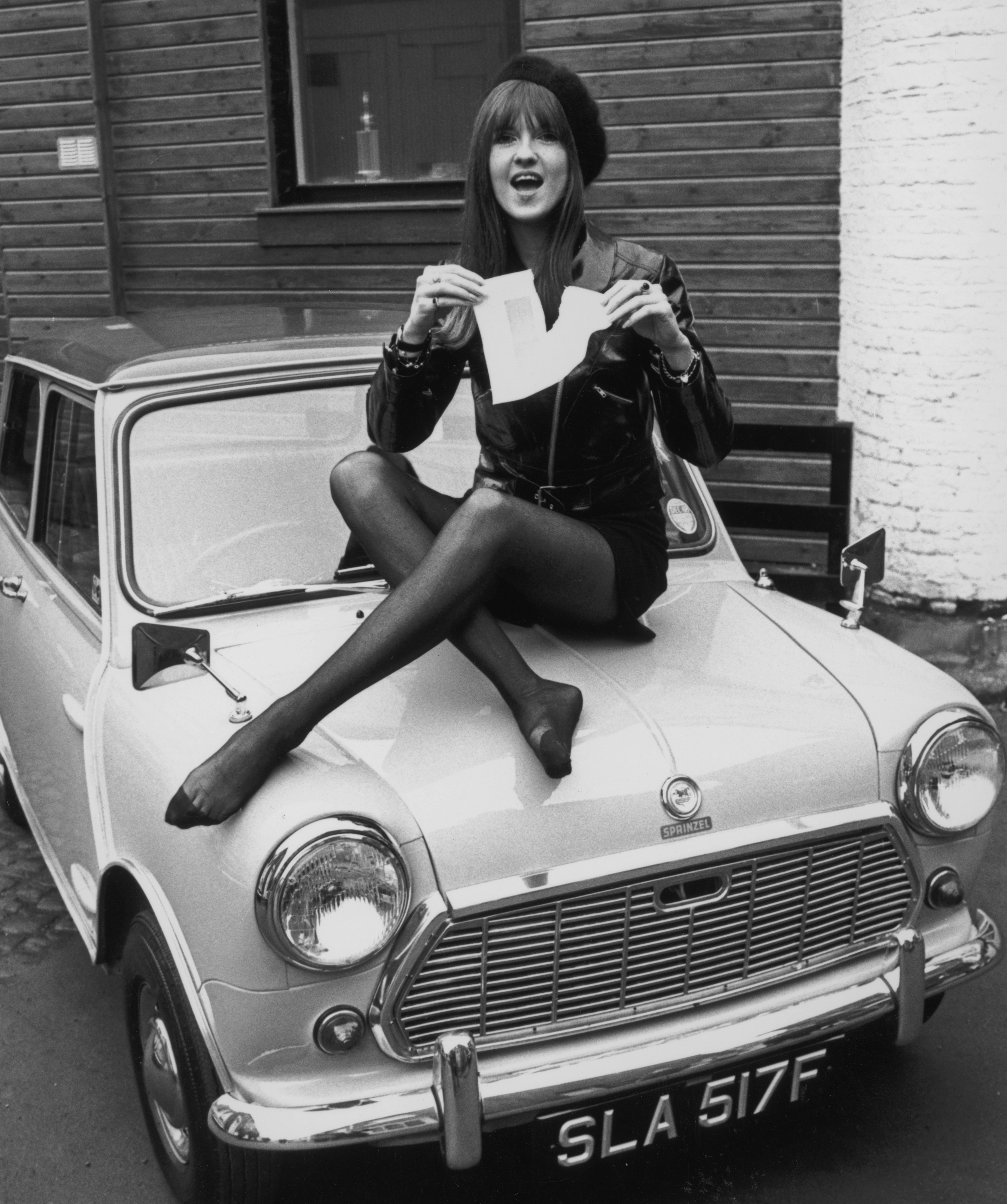 Cathy McGowan, presenter of the TV pop programme 'Ready Steady Go', tears up her 'L' plate after passing her driving test at the first attempt, 19th January 1968. She is sitting on the bonnet of her new Mini deluxe automatic, purchased from John Sprinzel's garage in Lancaster Mews at a cost of ?672. (Photo by Bob Aylott/Keystone/Hulton Archive/Getty Images)