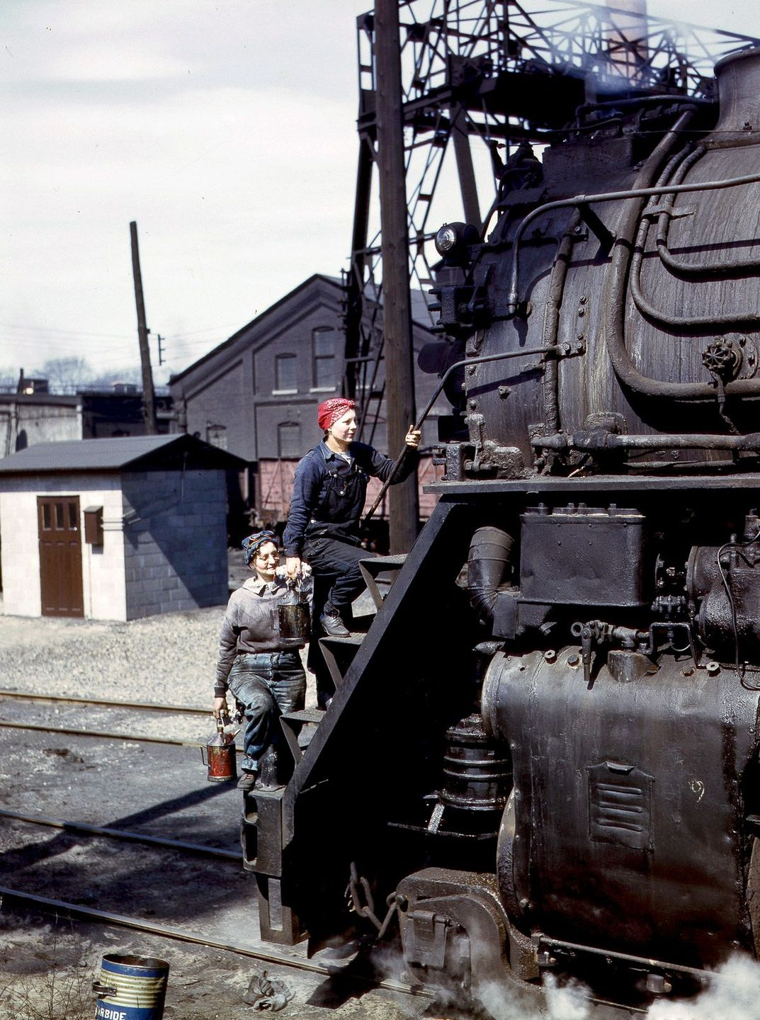 Mrs. Marcella Hart and Mrs. Viola Sievers clean an H-class locomotive.