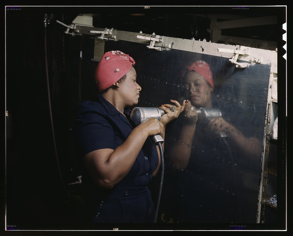 Operating a hand drill at Vultee-Nashville, woman is working on a %22Vengeance%22 dive bomber, Tennessee