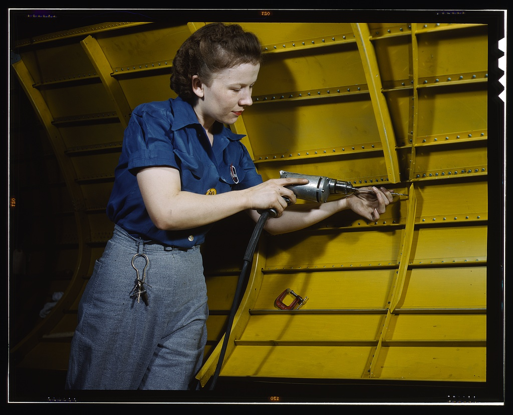 Operating a hand drill at Vultee-Nashville, woman is working on a Vengeance dive bomber, Tennessee