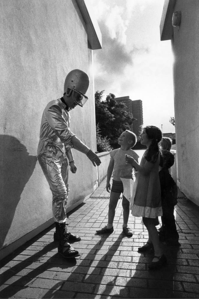 Jerry Dammers of Two Tone group, The Specials, entertaining a group of young children, dressed as an alien, UK 1980