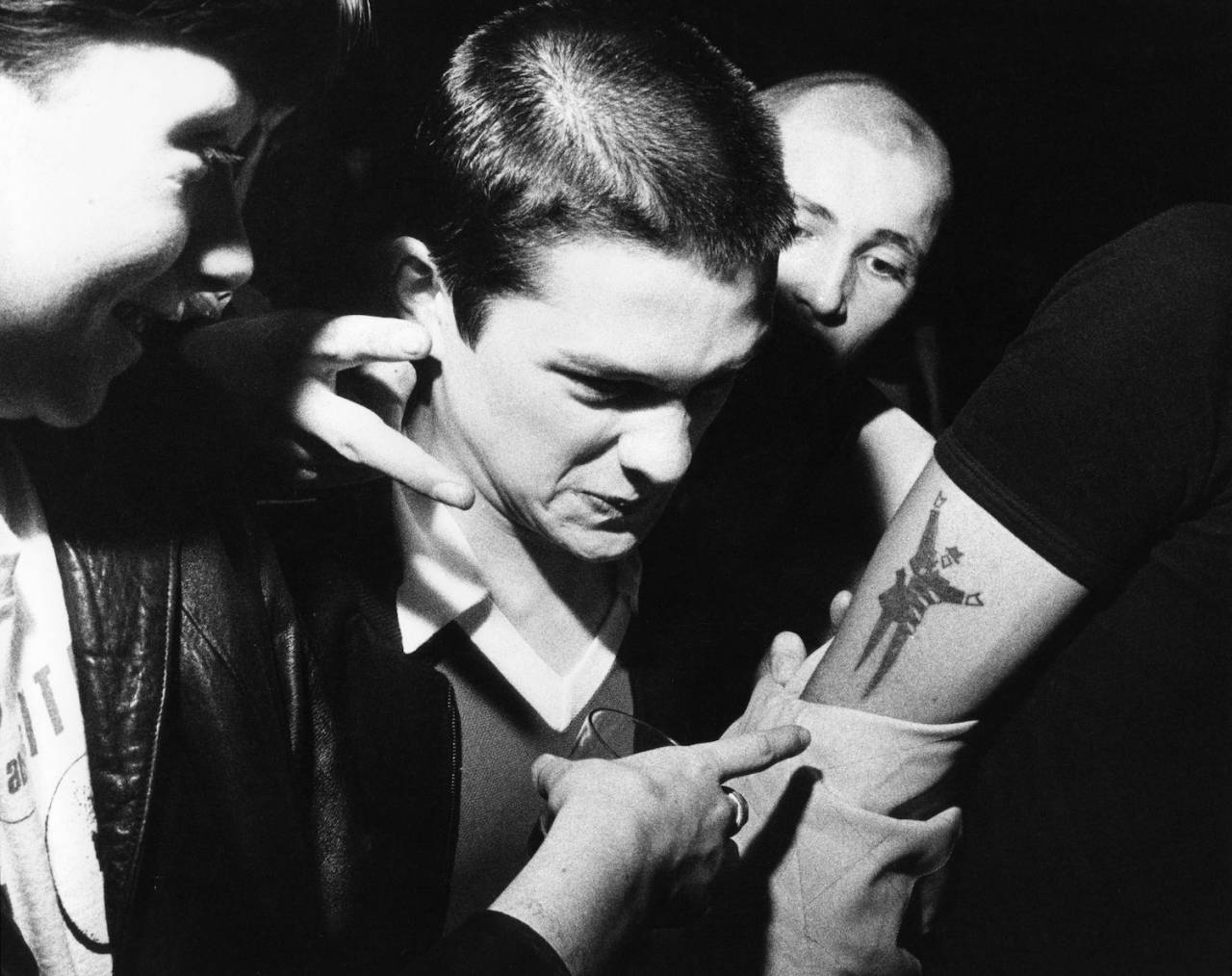 Skinheads pointing at a 2Tone Body Snatchers, tattoo, at a gig, UK 1980