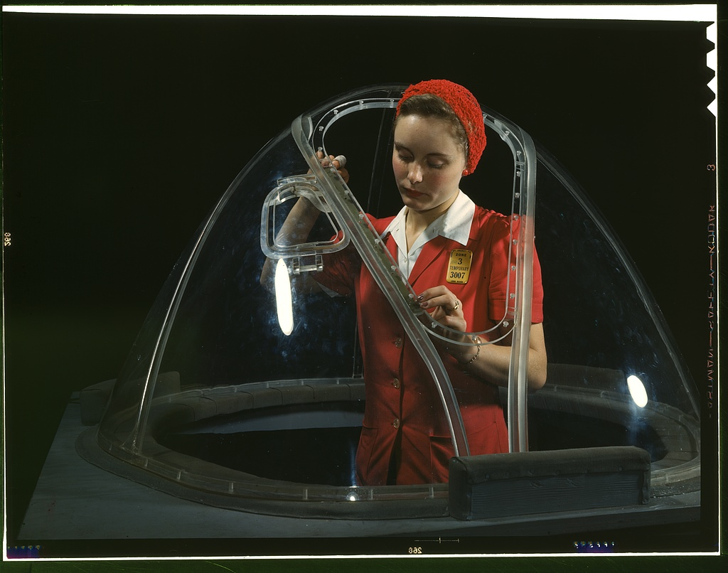 This girl in a glass house is putting finishing touches on the bombardier nose section of a B-17F navy bomber, Long Beach, Calif.
