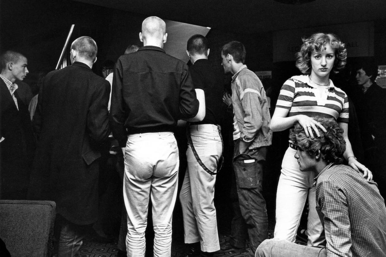 A couple at a gig with skinheads in the background, Ska, 2 Tone, UK 1980