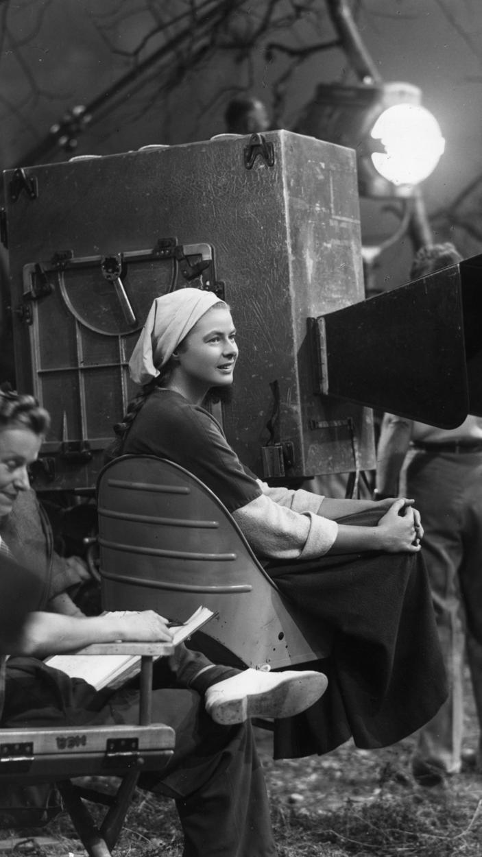 1948 - Actress Ingrid Bergman sits next to the camera during a break in filming on the set of director Victor Fleming's film Joan of Arc.
