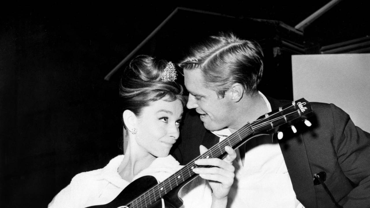 Audrey Hepburn strums a guitar for her costar George Peppard between takes on the set of Breakfast at Tiffany's on Dec. 7, 1960. Directed by Blake Edwards.
