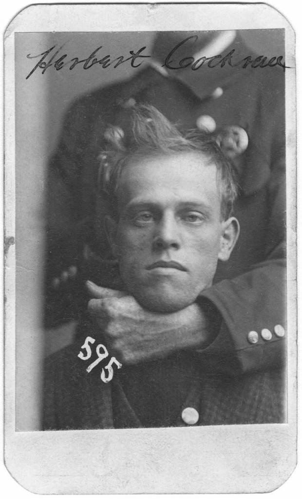 November 1899 An unidentified member of the Omaha police force holds Herbert Cockran in a headlock during his mug shot. Cockran was arrested on Nov. 24, 1899, for burglary. A tailor from Fairmont, Nebraska, Cockran had a slightly stooped build with a fair complexion and his eyebrows met at the root of his nose, according to the police description.