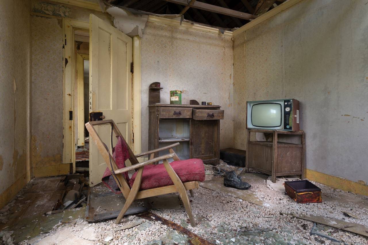 TV SET The screen of an old black and white television has survived intact while the walls and ceilings crumble around it.