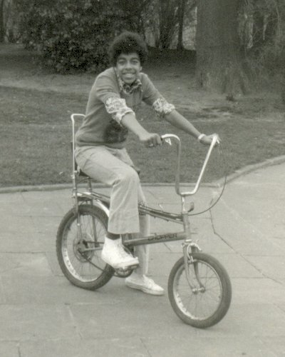 "Tony on a Chopper which was the coolest bike in Britain to have in the mid-70s. The Raleigh Chopper was a wheelie bike, manufactured in the 1970s by the Raleigh Bicycle Company of Nottingham, England. Its unique design became a true 70s cultural icon. The Chopper bike was based on the look of a customised chopper motorcycle, made popular with films such as Easy Rider, and it was the ""must have"" item and signifier of coolness for many kids at the time."