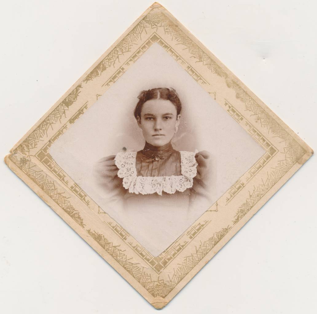 """Here is a photograph that is everything I like about the diamond photographs. The oversize image dominates its space (and the dark tone overpowers the lighter tone of the surrounding card mount). The woman gazes directly at the camera. The lace collar of her dress provides an additional frame for her beautiful, intense face. I've had this image for a while, which means that it most likely comes from west of the Mississippi. Life, in that place, at that time, was hard, difficult at best. It could be brutal. """"I'm up to the task,"""" she seems to say. Her name was Ada Church. [Ada Church]"""