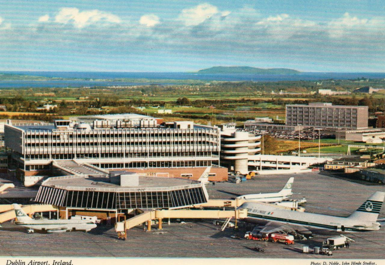 "Dublin Airport Postcard published by John Hinde Ltd, ca 1970s Photo by D. Noble, John Hinde Studios. We bought the postcard in Dublin, 1978 ""DUBLIN AIRPORT, situated six miles from the city centre is the home base of Aer Lingus Irish International Air Lines and is linked by direct services with the principle cities of Europe and the United States of America. Dublin City stands at the foot of the Wicklow mountains, facing Dublin Bay and is famous for its magnificient Georgian architecture and spacious streets. Passengers on the Trans Atlantic flights from Dublin may also avail of the duty free bargains at the Airport shops"" - text on backside of postcard."