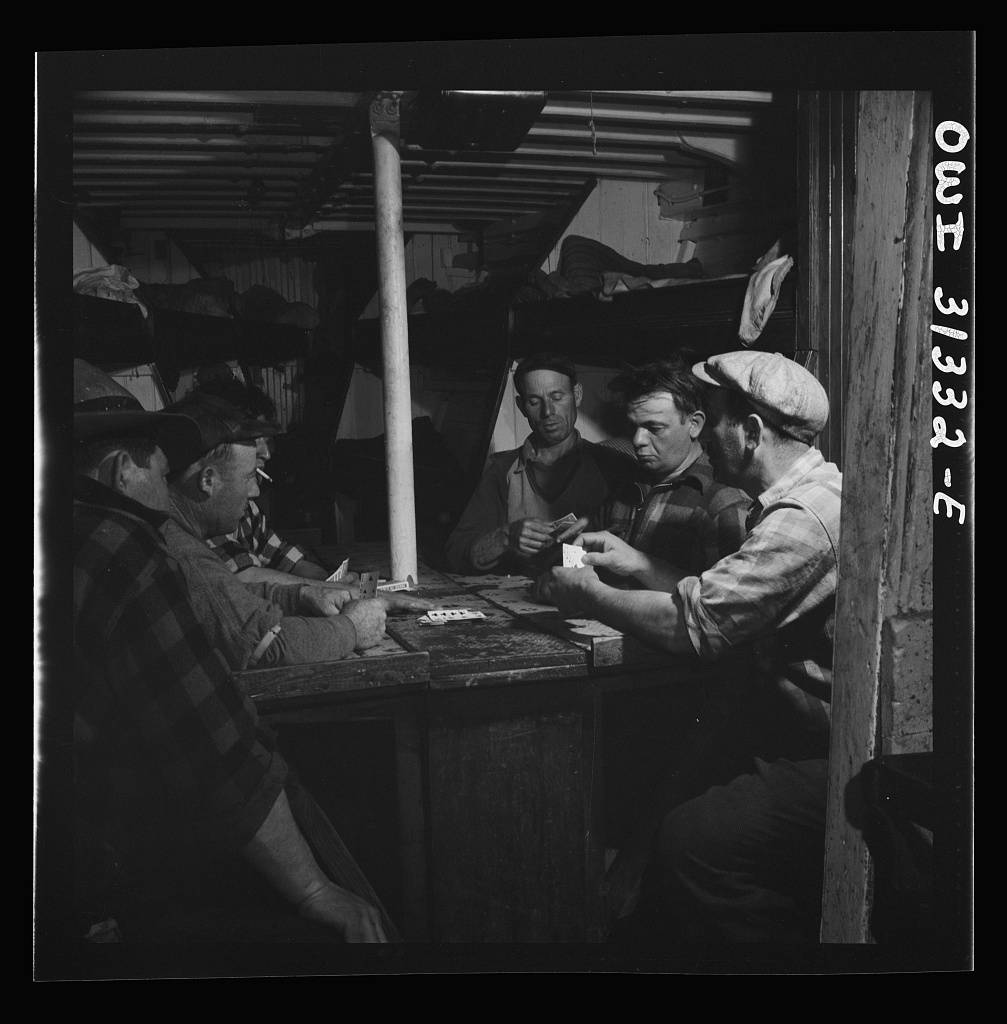 Men playing cards as the ship heads home with a hold full of fish