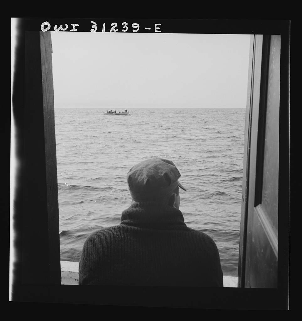 The dories pulling in their nets, seen from the mother ship's cabin window