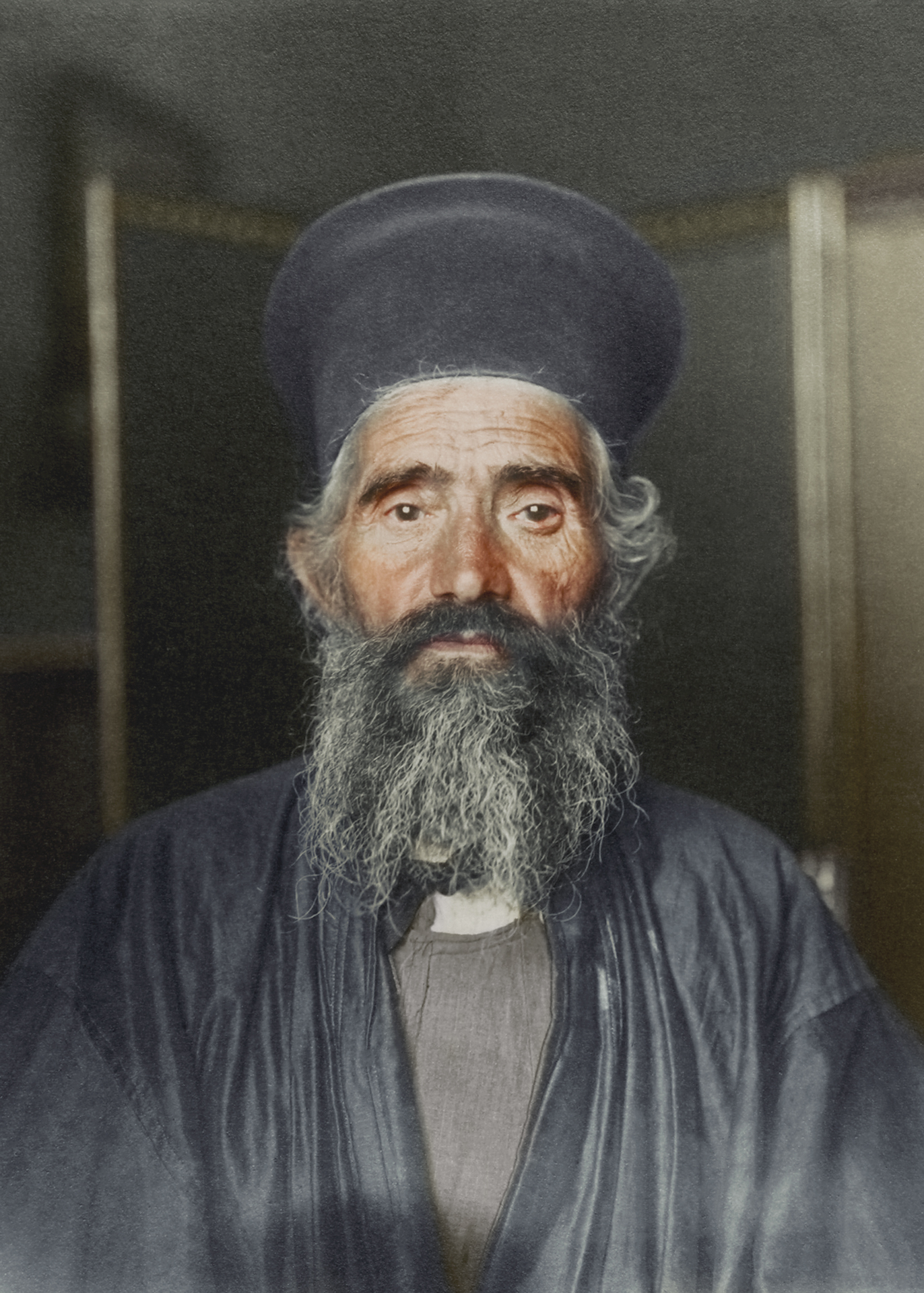 "c. 1910 ""Rev. Joseph Vasilon, Greek-Orthodox priest."" The vestments of the Greek Orthodox church have remained largely unchanged. In this photograph, the priest wears an anteri, an ankle length cassock (from the Turkish quzzak, from which the term 'Cossack' also derives) worn by all clergymen over which an amaniko, a type of cassock vest is sometimes worn, over which the black outer cassock known as a exorason is worn. The stiff cylindrical hat is called a kalimavkion worn during services."