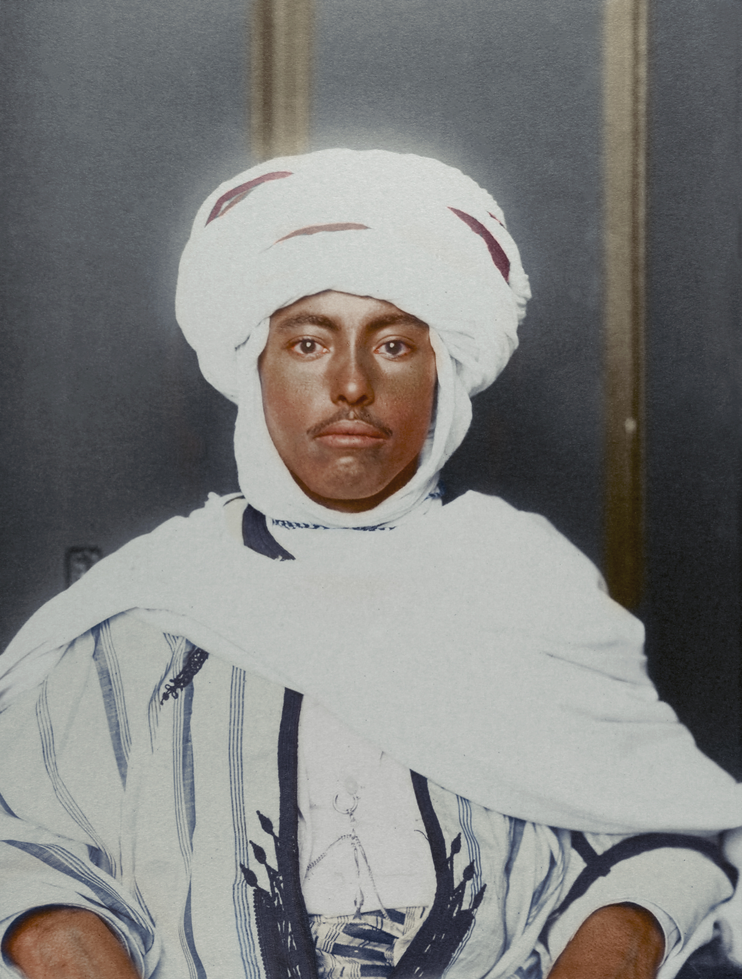 "c. 1910 ""Algerian man."" It is noted that Algerian identity is shaped by its indigenous Berber, Arab, African and Mediterranean cultures. The kufiya is a square of fabric folded into a triangle and set upon the head by an 'iqual - a circlet of camel hair. The kaftan tunic has been worn by many cultures and was often made of wool, silk or cotton - though the cloak, known as a burnous was made from woolen fabric and came with a hood and was either white to a dark brown depending on the region."