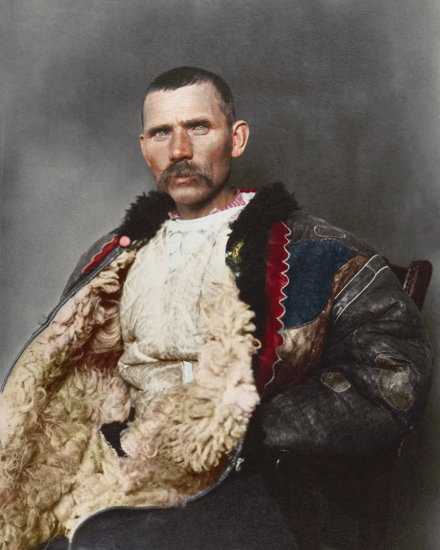 "1906 ""Romanian shepherd."" Dominating the photograph is a traditional shepherd's cloak known as sarică, made from three or four sheepskins sewn together with the fleece facing outwards and were generally extended to below the knee, which could be used as a pillow when sleeping outdoors. Sheepskin was also used to make the shepherd's cojoc, an embroidered sleeved coat that had tassels, leather strips and other small decorative elements added. This particular example given the ornamentation wasn't likely used for practical purposes given the amount of decoration adorning it."