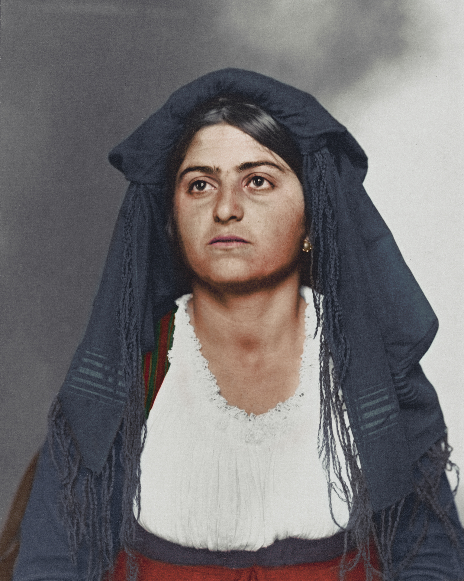 "c. 1910 ""Italian woman."" This traditional dress was most likely homespun and consisted of a long, wide dress to cover the ankles. Above, a bodice and sleeves were tied in such a way to expose portions of the linen blouse and colours and materials were usually regional. Shawls and veils were also a common feature, and an apron decorated with floral brocades were used for special occasions such as weddings."