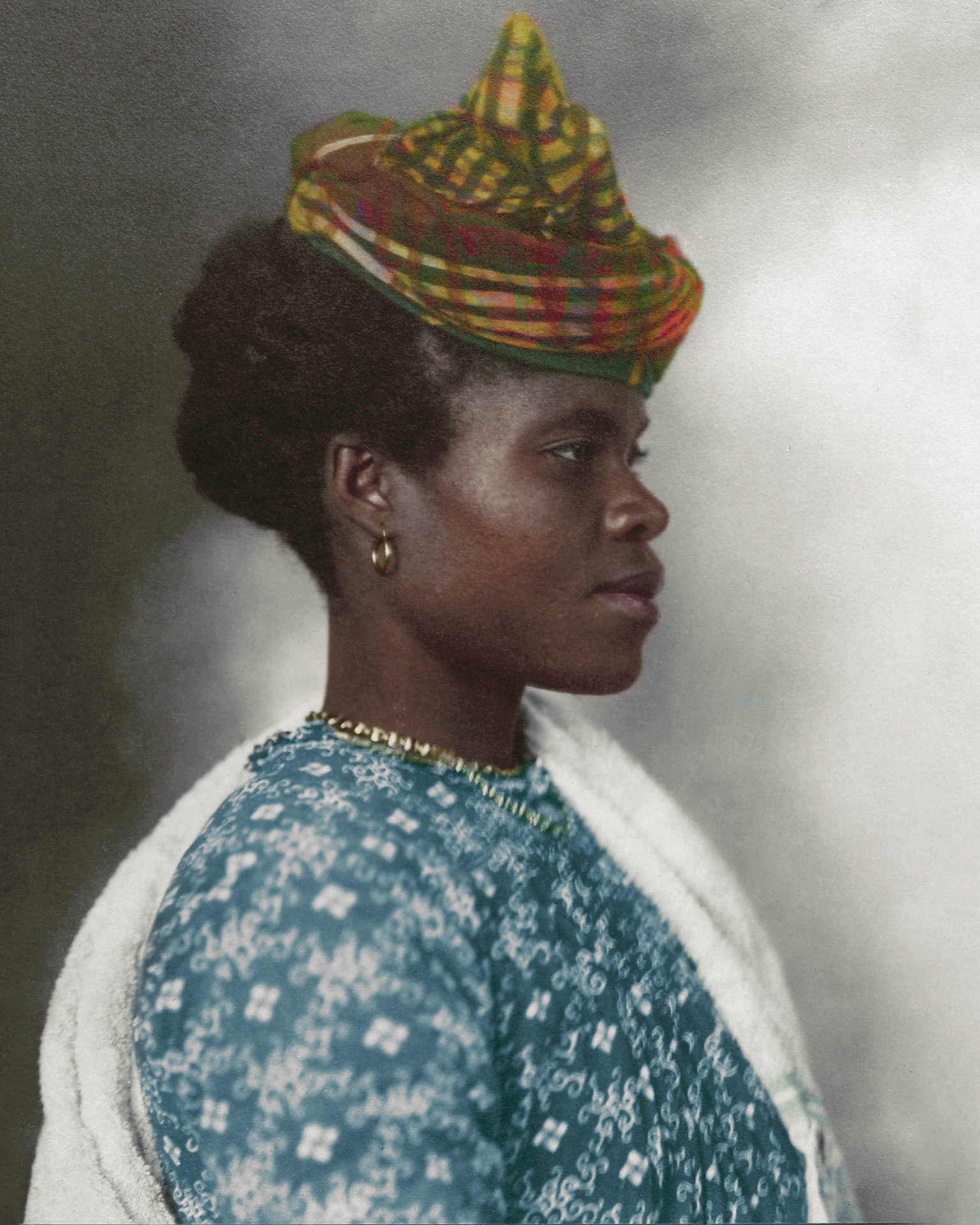 "1911 ""Guadeloupean Woman."" The elaborate tartan headpiece worn by Guadeloupean woman can be traced back to the middle ages where the eastern Indian city of Madras was famed for its cotton making. First plain, then striped and then with increasingly elaborate patterns, the Madras fabric that was exported and used as headwraps was eventually influenced by the Scottish in colonial India, leading to a Madras inspired tartan known as 'Madrasi checks', which in the colonial empires made its way to the French occupied Caribbean. Like many of the traditional costumes from all over the world, the headpiece decoration in many cases was indicative of the married status of the wearer."