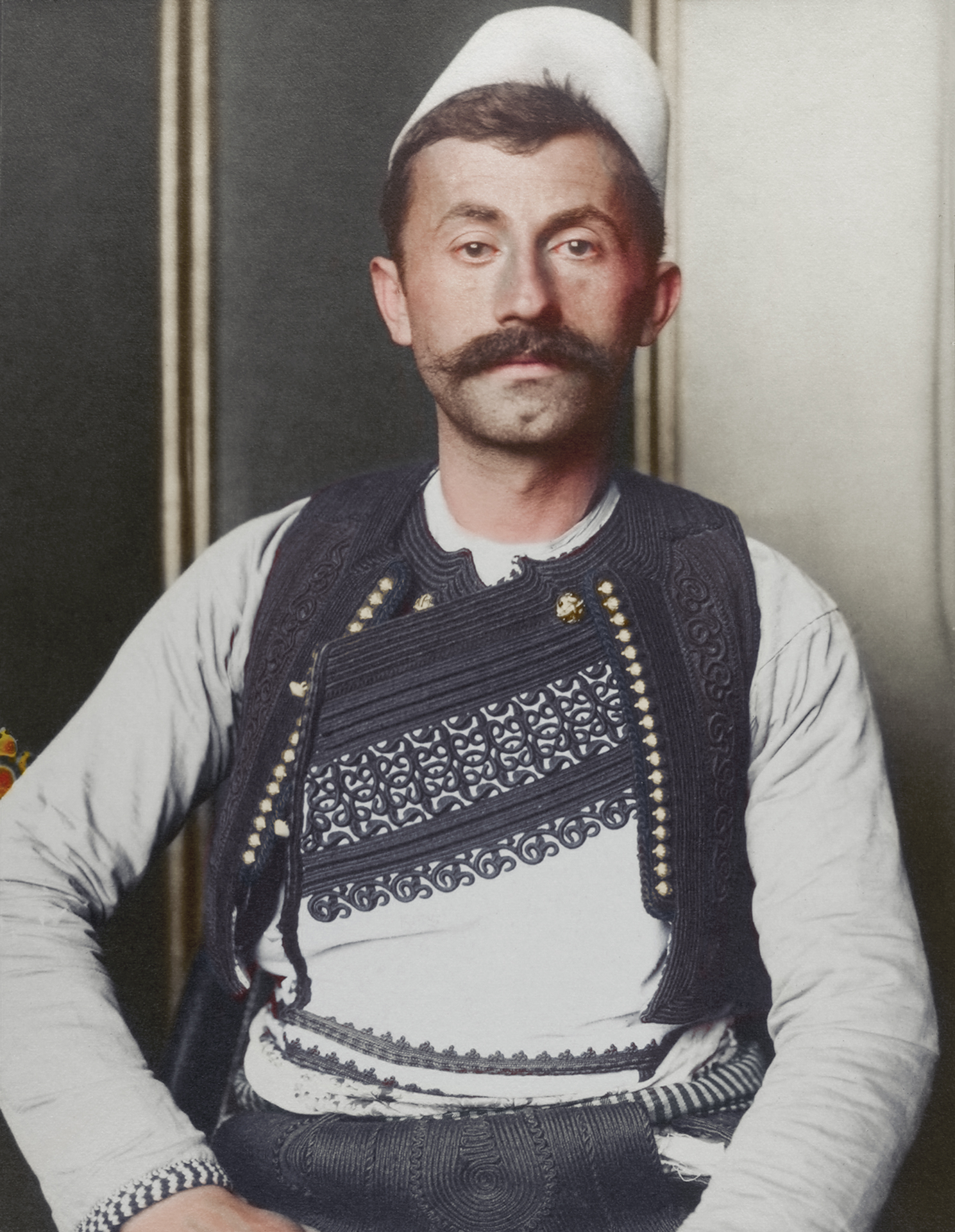 "c. 1910 ""Albanian soldier."" The truncated brimless felt cap is known as a qeleshe, whose shape was largely determined by region and moulded to one's head. The vest, known as a jelek or xhamadan was decorated with embroidered braids of silk or cotton, its colour and decoration denoted the region where the wearer was from and their social rank. Most likely, this soldier is from the north eastern regions of Albania judging by the cut and colour of his outfit."