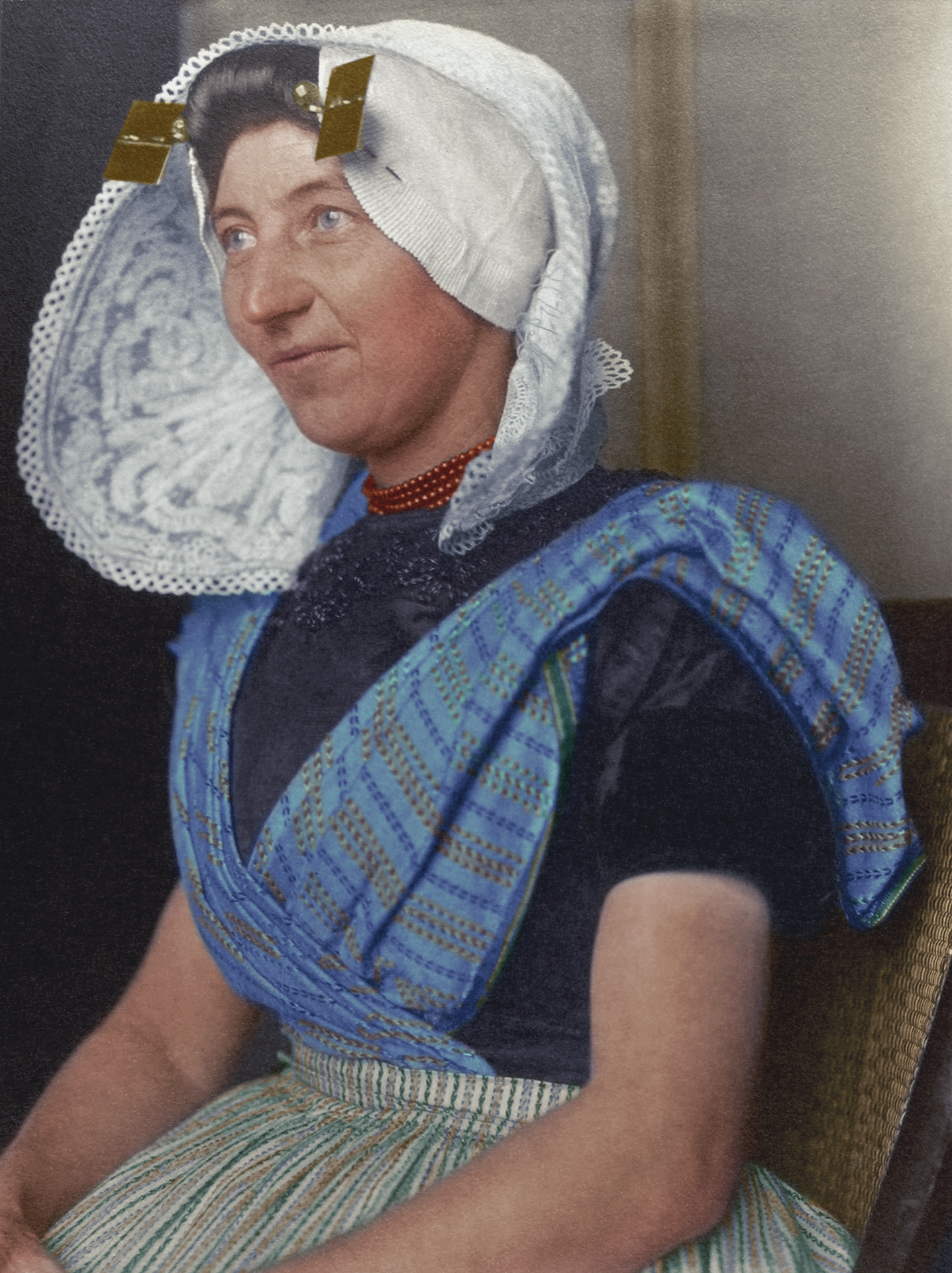"c. 1910 ""Dutch woman."" The large bonnet which arguably is one of the most recognisable aspects of Dutch traditional dress was usually made of white cotton or lace and sometimes had flaps or wings, and often came with a cap. The square stukken and golden pins denoted her marital status and that she was a Protestant. The rest of the costume, again like so many others came in distinctly regional variations were made from cotton, linen or wool, decorated with embroidered floral patterns. A sleeved bodice covered the top half of the body and came in a dark colour, contrasted by a colourful tunic as seen in this photograph."