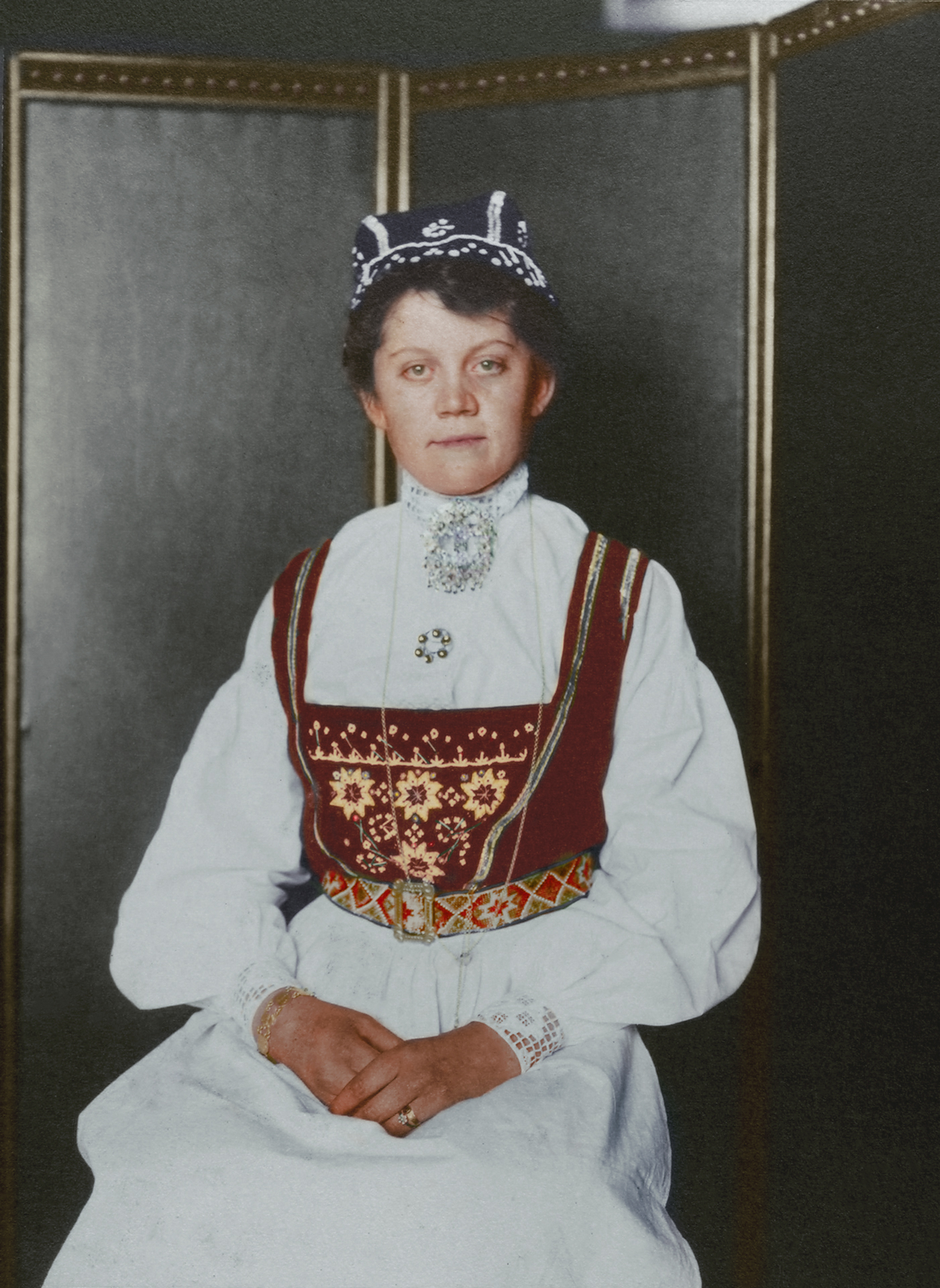 """Norwegian woman."" Bunad is the umbrella term encompassing Norwegian traditional dress that is distinctly Norwegian, though the costumes themselves like so many others are influenced by region, tradition and available material. In rural Norway, clothes were often made at home and typically made from wool, though silk or other imported material was available. Decoration was elaborate or sparse depending on the region, or whether or not the dress was considered Sunday best. In much of rural Norway, women often covered their hair as a sign they were married."
