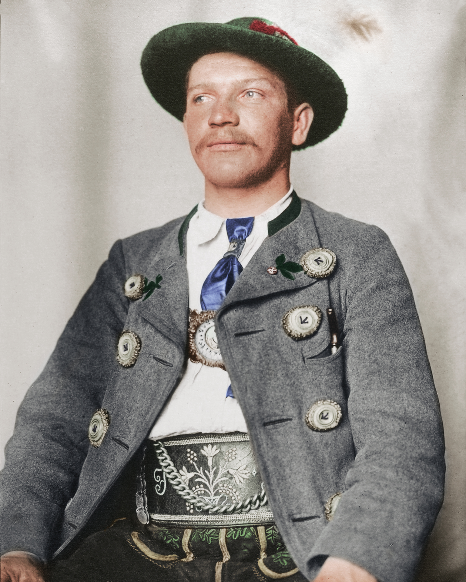 "c. 1910 ""Bavarian man."" The traditional dress of Germany is known as the trachten, like so many others has regional variations. In the alpine regions of Germany like Bavaria, leather breeches known as Lederhosen were worn regularly by rural folk, though in modern day Germany, most people associate the garment with the annual Oktoberfest. The grey jacket, known as a trachtenjanker is made from fulled wool and decorated with horn buttons, often used by hunters in the region."