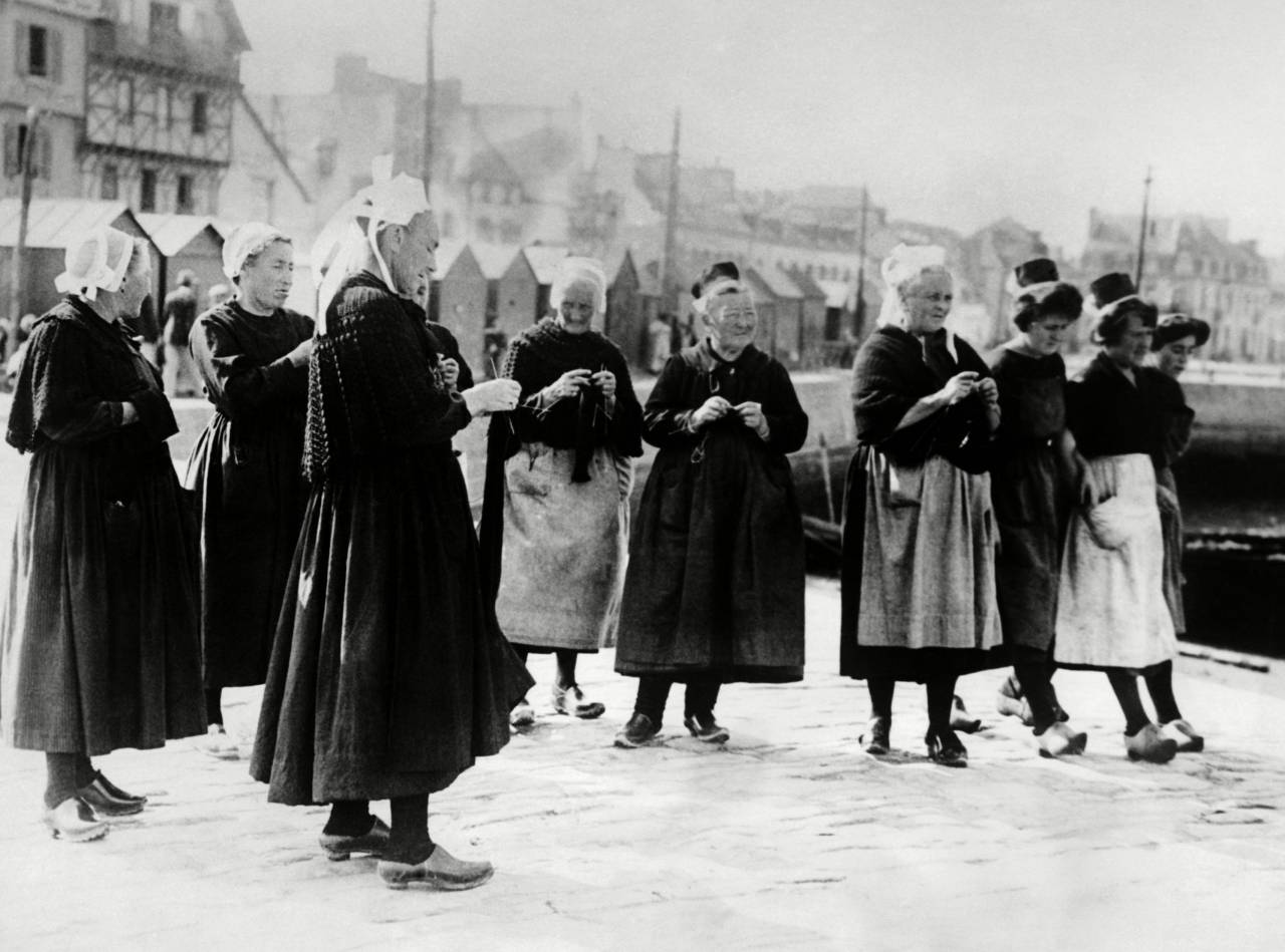Wearing the unique costumes of Brittany, France, wives knits as they await the return of their fishermen husbands. Oct. 1926. (1536) Wearing the unique costumes of Brittany, France, wives knits as they await the return of their fishermen husbands. Oct. 1926.