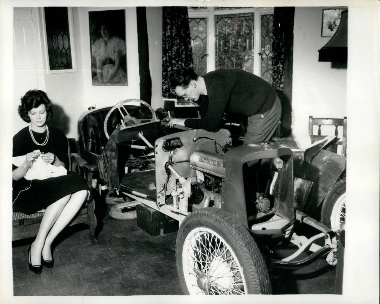 1966 - Vintage Car In The Gidding's Drawing Room: For three months Mrs. Christine Giddings has had the bits and pieces of a vintage motor car cluttering up her best drawing room. Her car enthusiast husband, Peter, is assembling a car in which he hopes tor race, and the only suitable place he had to be it as drawing room. Scheduled to be finished in April, the car will have to be taken down again to get it out of the Giddings Old Portslade, Sussex, home. The chassis is built from vintage Frazer - Nash parts and the engine is pure Atlanta - Gough. When It's finished, the car will have cost Mr. Giddings over ~£250 - not counting the hours of labour he has put into it himself - but he hopes that it will do a maximum speed of 120 mph when it's on the road.. Christine gets on with her knitting in an arm - chair in the drawing room - while Peter gets on with the car.