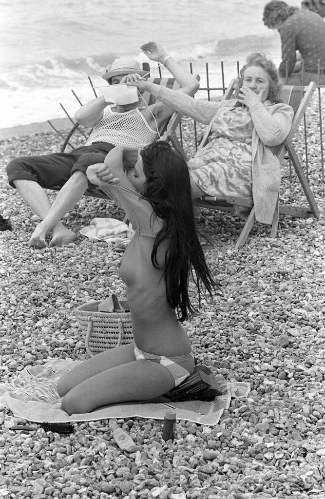 WOMAN COVERING MANS EYES WITH HER KNITTING AS A YOUNG WOMAN TAKES OFF HER TOP ON THE BEACH WOMAN COVERING MANS EYES WITH HER KNITTING AT SIGHT OF YOUNG WOMAN TAKING OFF HER TOP ON THE BEACH - 1974