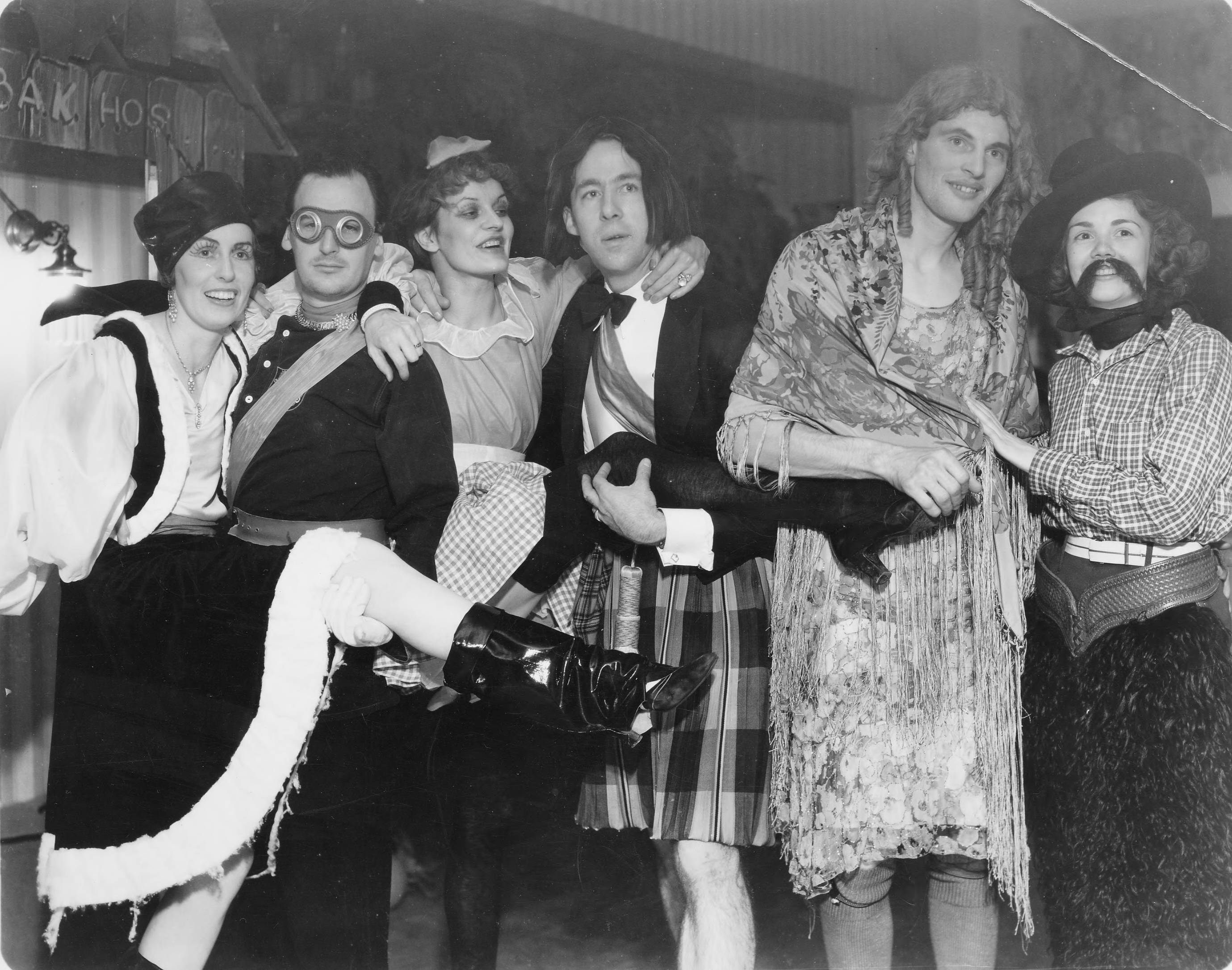 Members of the Tacoma Country and Golf Club reveled at a masquerade ball at the clubhouse on Halloween, 1934. In the center in kilts with wig askew was future Mayor of Tacoma Harry P. Cain. To the far left was his wife, Marjorie Cain, dressed as a Russian cossack. Cain was holding the leg of an unidentified French maid, as an unidentified aviator held that of his wife in this interesting picture. The unidentified cross dressing couple to the right smiled merrily at the camera.
