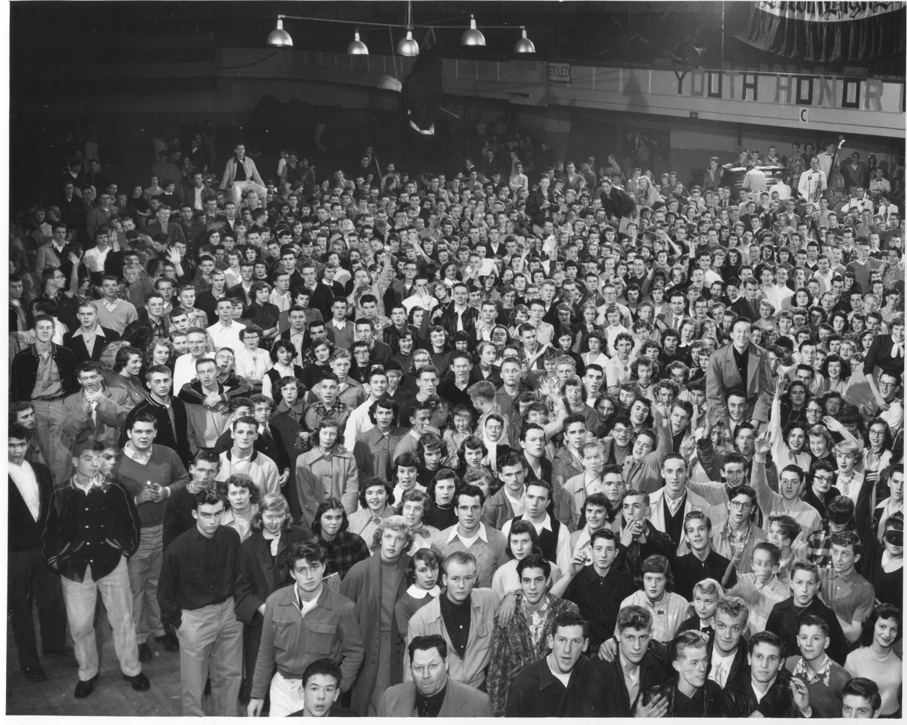 This photograph shows part of the crowd of 2,800 teenage Tacomans who spent their Halloween evening in 1951 at the Tacoma Armory, 715 South 11th Street. Working with the Metropolitan Park District and the Tacoma Police, the Tacoma Moose Lodge sponsored the third annual all-city high school dance to give Tacoma's young people someplace safe to go after dark. The dance was from 8 to 11:30 p.m. with music provided by Larry Carino and his orchestra, one of the best 10 piece bands in the area. Police later said that the evening was one of the quietist on record.