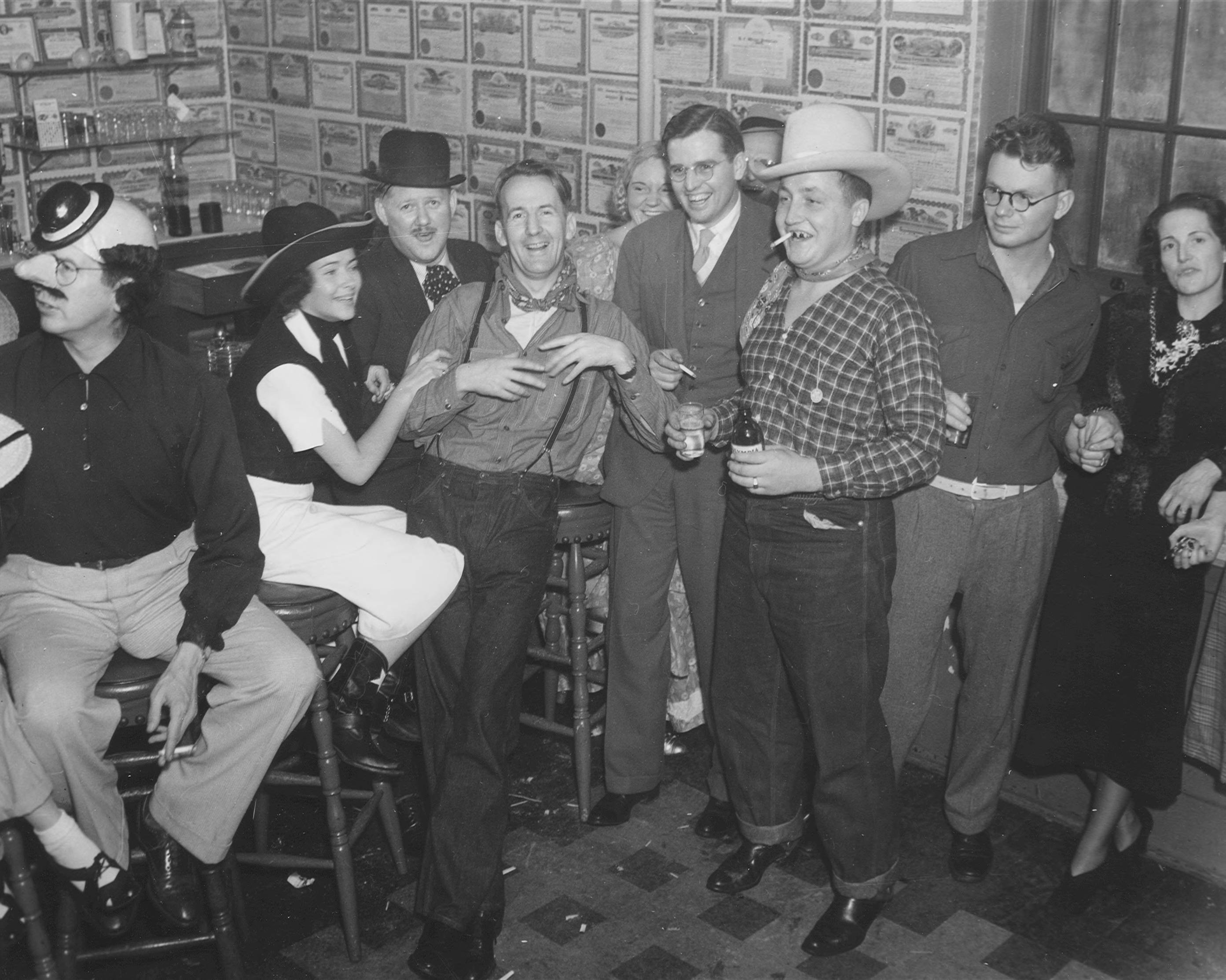 On October 30, 1937, a Halloween barn dance was held at the Tacoma Country & Golf Club. Among the partygoers gathered around the bar were Caroll Carstens (second from left), Ed Griffin (fourth man from left), Tom Carstens (in cowboy hat), and Bud Doherty (second from right). The walls of the bar are papered with stock certificates. This decorating idea was the brainchild of Club president Harry K. Todd. The walls are papered with about 8 million dollars worth of stock certificates from businesses and ventures that did not work out. (T.Times, 11-30-1937, Society, p. 11).