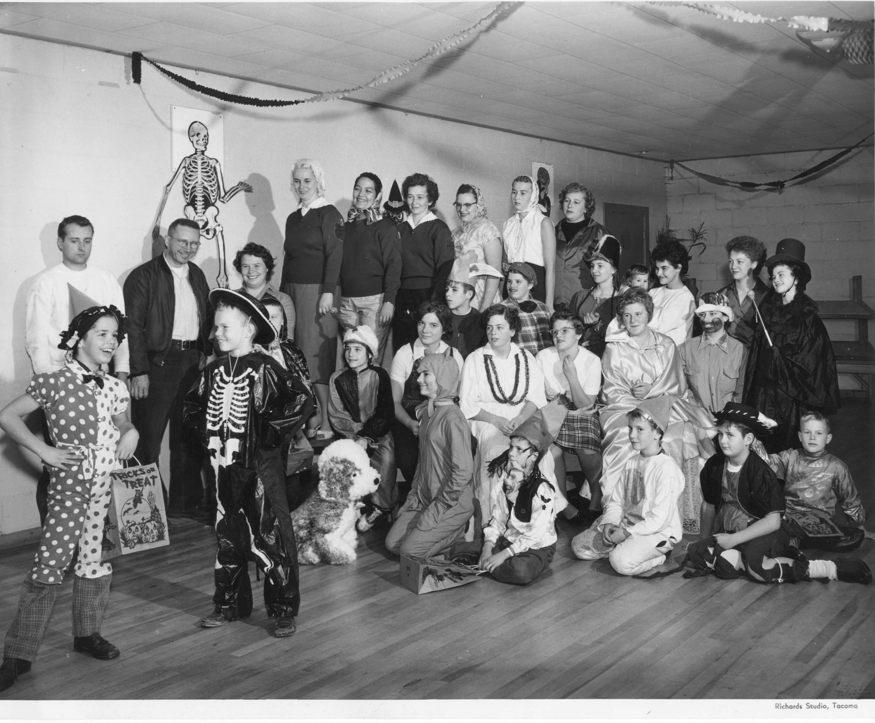 On October 31, 1959, two boys, Patrick on the left and David on the right, modeled their costumes for a group of approximately 20 children and assorted adults at a Halloween party held at the Blue Barons Motorcycle Clubhouse, 5623 South Monroe Street. David is dressed in a shiny black skeleton costume topped with a cowboy hat and Patrick wears a clown outfit that is a few sizes too small. The children reside at St. Ann's Home and they are receiving gifts and treats at this party hosted by the Blue Barons. St. Ann's Home was an orphanage located at 6602 Alaska and run by the Sisters of St. Francis.