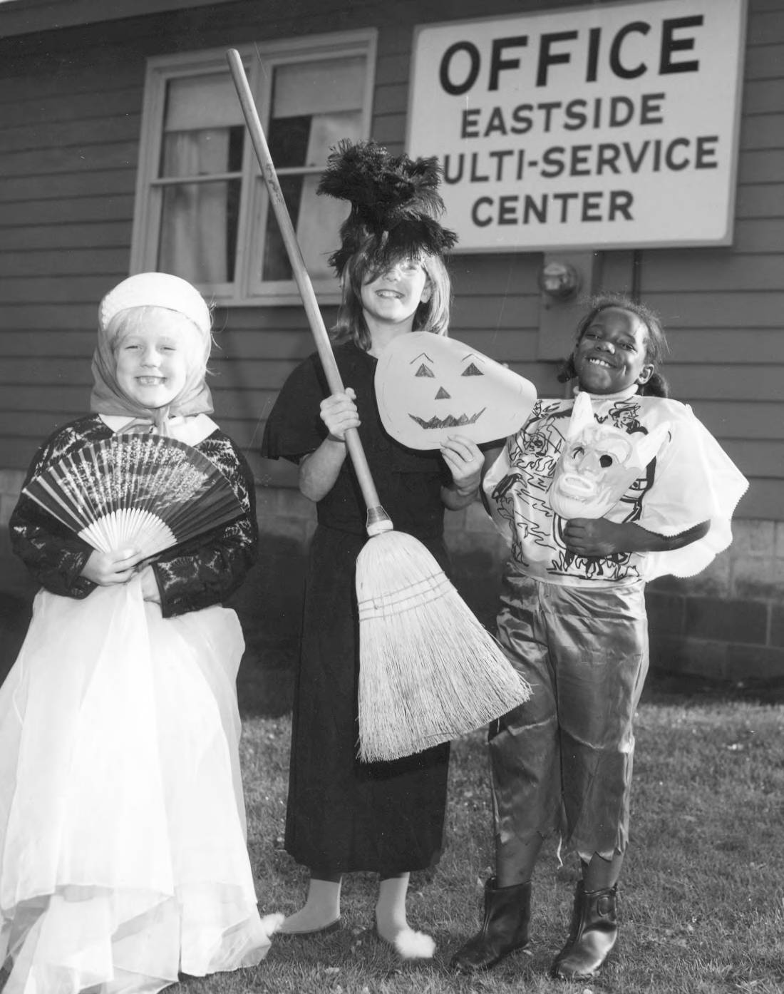 "Description""Official Witch"" Chari-Kee Rowell, age 10, is flanked by her court, ""Official Princess"" Darcy Orr and ""Official Devil"" Janet Barr, as she prepares to lead the first Eastside Halloween Torchlight Parade which will be held on October 31, 1968. They are standing in front of the office of the Eastside Multi-Service Center, an arm of the Tacoma-Pierce County Opportunity & Development, Inc. Alice Dunn, director, had recently announced that the Eastside Youth Center in Salishan, destroyed by fire on March 30th, would be open in time for the ""biggest Halloween party ever held in the Eastside."" An anonymous donor had just pledged $2,000 to complete the building fund. Hundreds of children dressed as goblins, ghosts and fairy-tale creations were expected to assemble at Gault and Roosevelt elementary schools to march in two torchlight one-mile parades culminating at the new Eastside Youth Center where they would bob for apples, hunt for pennies in the hay, eat pies and have their costumes judged for prizes."