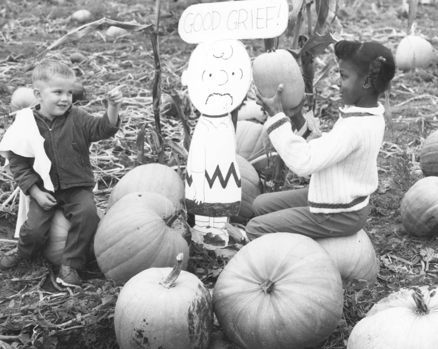 "Frank Temple, sitting on a large pumpkin, appears to approve Joann Glenn's selection of a nicely shaped, small pumpkin. Frank, Joann and ""Charlie Brown"" were photographed in Mr. and Mrs. Eberhard Kaelin's pumpkin patch at Valley Avenue and 54th Avenue East in Fife on October 22, 1968. Charlie Brown seems to be commenting on the dilemma of picking out just the right pumpkin for Halloween. Frank is the son of Mrs. Ethel Temple and Joann is the daughter of Mr. and Mrs. Eugene Glenn. (Photograph ordered by the Tacoma-Pierce County Opportunity & Development, Inc.) (TNT 10-25-68, A-11)"