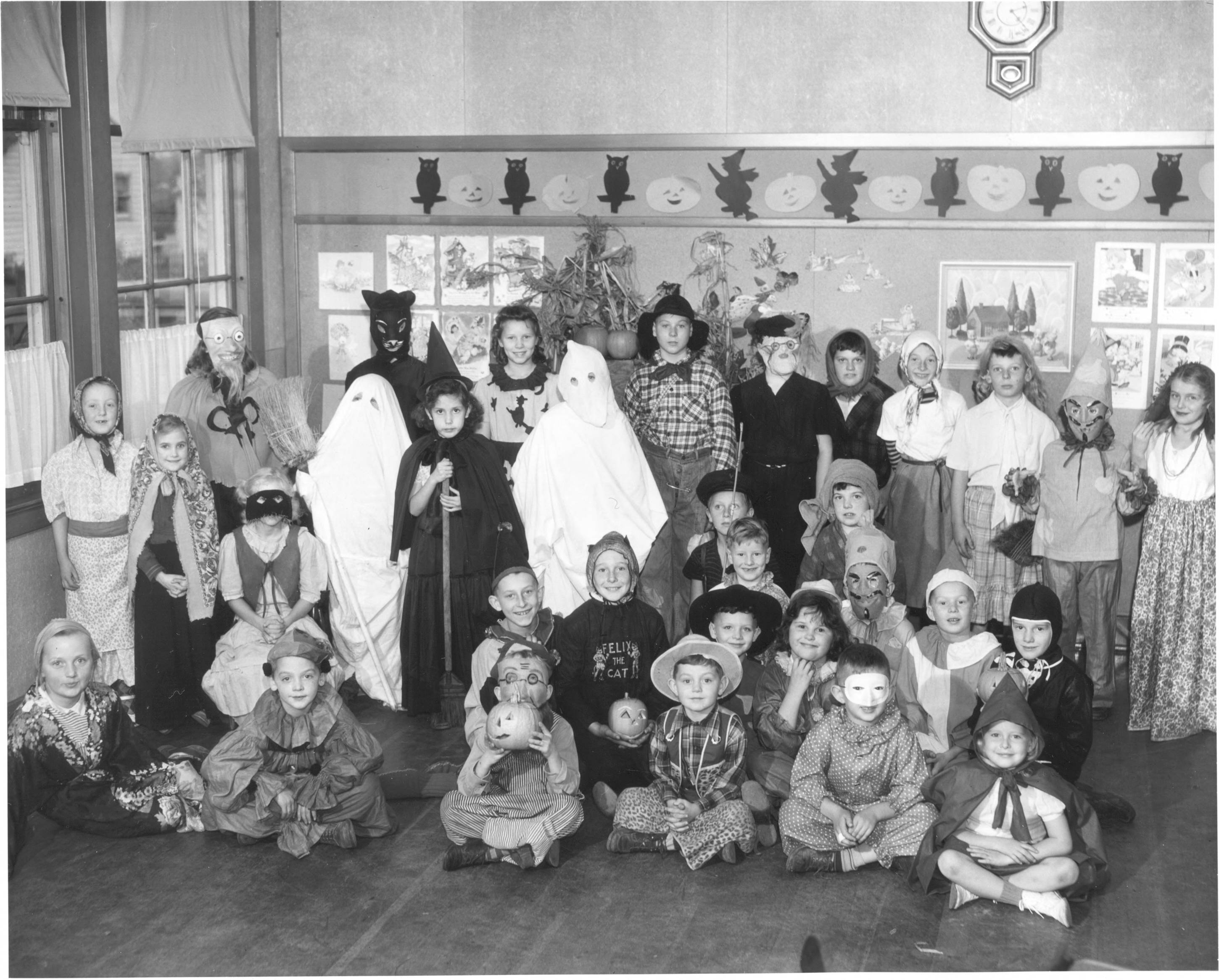 "Children at Manitou School are celebrating their tenth annual Halloween festivities with costumes, masks, parades and special tricks and treats. View of children dressed as, fortune tellers, cowboys, indians, witches, hillbillies, ghosts, scarecrows, clowns and ""Little Red Riding Hood"". Jack-o-lanterns, witches and owls decorate the walls of the classroom, names appear in newspaper (T. Times, 10/31/47, p. 16)."