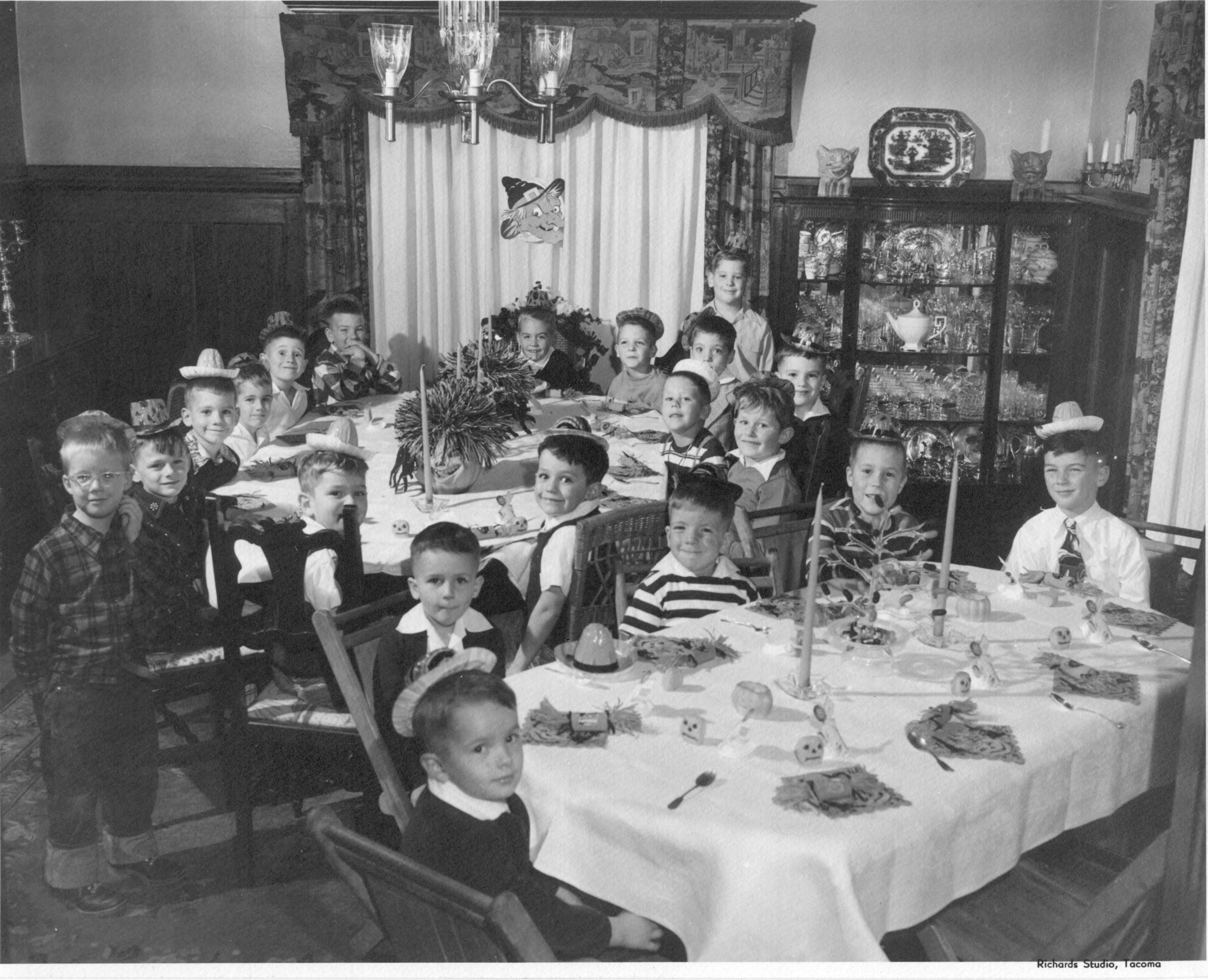 20 children have gathered for a Halloween Party. They are seated at two tables in a formal dining room with dark wood wainscoting, heavy draperies and a china cabinet full of glassware. Halloween decorations are seen on the tables, on top of the china cabinet and a witches' face is pinned to the curtain. Many of the boys wear party hats.