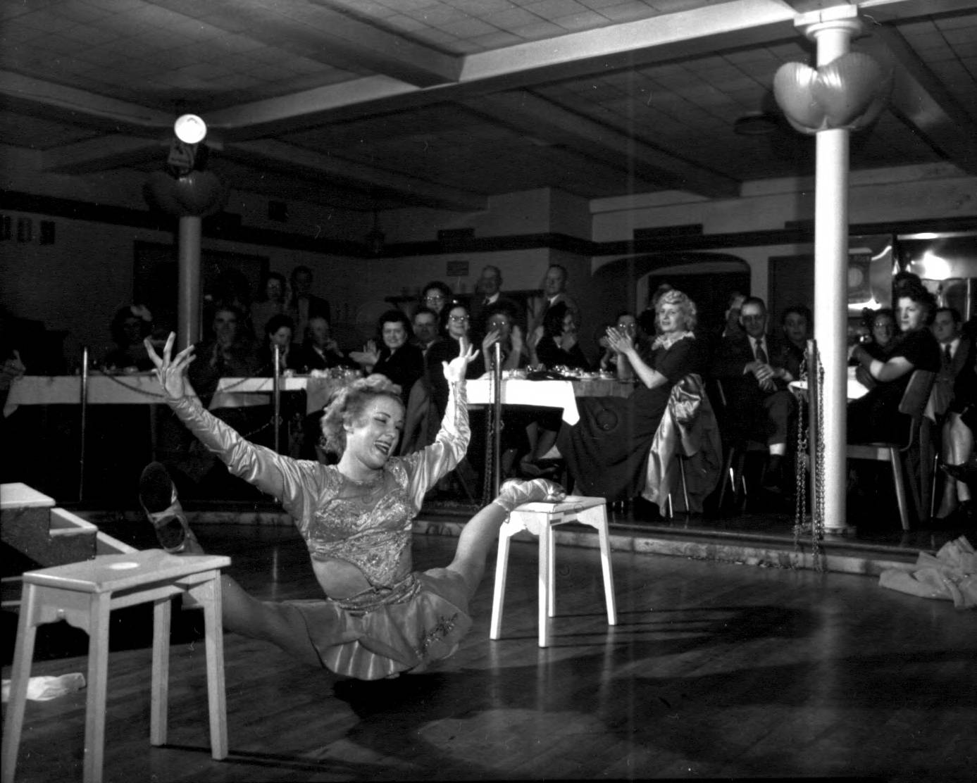 A woman contortionist performed on the dance floor with her legs elevated on two tables on either side of her body in a split formation. Her body is lower than her feet. Groups of people who are seated at tables around dance floor applaud her performance during the Halloween party sponsored by the Tacoma Athletic Commission at the Top of the Ocean.